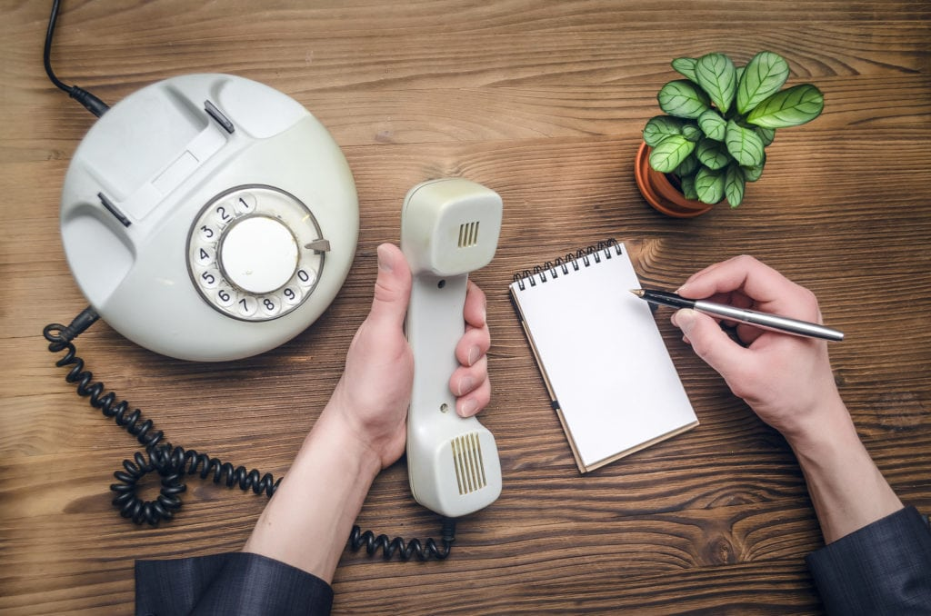 Telephone in male businessman hands and notebook with copy space on office table. Contact us. Business conversation.